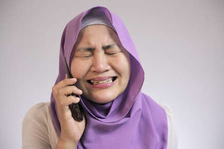 Portrait of young Asian muslim woman crying sad by phone call, worried expression. Receiving bad news on phone concept