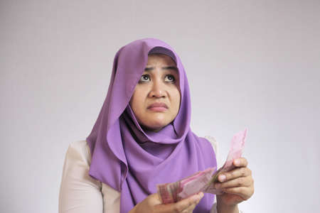 Confused stressed Asian muslim woman holding Indonesian rupiah cash in hand, thinking wondering how to spend. More money more problems  or not enough money concept