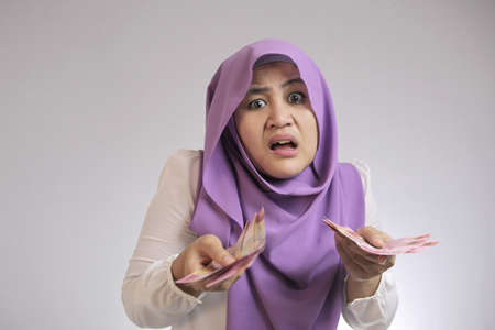 Portrait of Indonesian muslim woman looked confused with her rupiah money, complaining too small salary concept