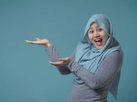 Portrait of Asian young happy muslim woman looking at camera smiling and pointing to presenting something on her side, with copy space Banco de Imagens