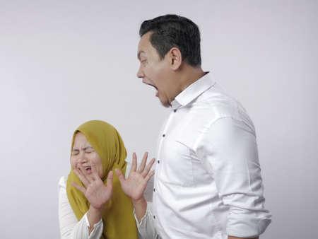 Retrato de marido y mujer de pareja musulmana asiática teniendo pelea, esposa temerosa de su marido, marido gritando, mala relación en concepto de matrimonio
