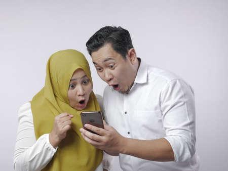 Porträt eines asiatischen muslimischen Paares schockiert oder überrascht, etwas auf dem Smartphone, großen Augen und offenem Mund zu sehen Standard-Bild