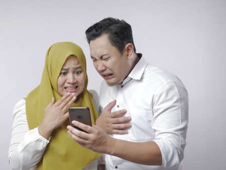 Portrait of muslim couple shocked and worried to see bad news on smart phone 免版税图像