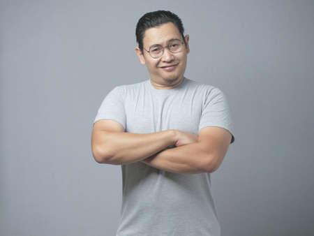 Foto immagine ritratto di divertente giovane attraente carino uomo asiatico sorridente felicemente, con le braccia incrociate