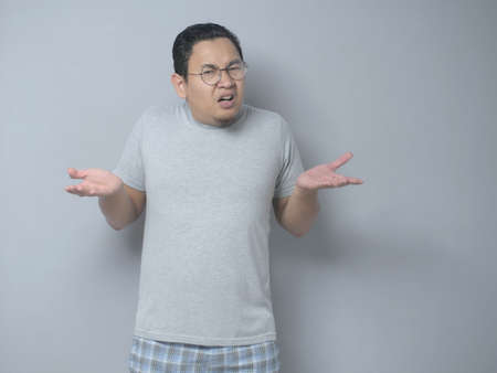 Portrait of funny Asian man with shrug shoulder up gesture, showing i don't know or rejection