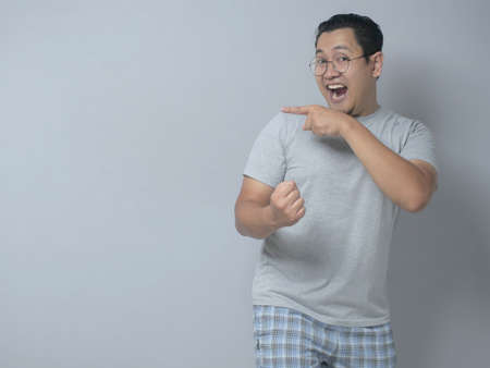 Portrait of funny young Asian man smiling and pointing to presenting something on his side, against grey background with copy space 版權商用圖片