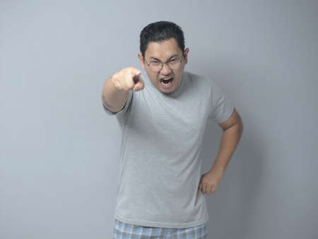 Portrait of funny Asian man showing cynical unhappy angry facial expression pointing forward giving warn, with selective focus Archivio Fotografico - 133177023