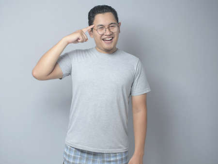 Portrait of smart good looking Asian man smiling at camera and pointing on his head, idea intelligence and imagination concept Archivio Fotografico - 133177024