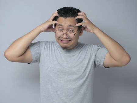 Il giovane asiatico sembrava frustrato per avere mal di testa, espressione di stress. Ritratto ravvicinato su sfondo grigio