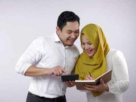 Portrait of Asian young muslim couple checking analyzing their family financial management report, young family housband and wife happy to see their financial plan Imagens