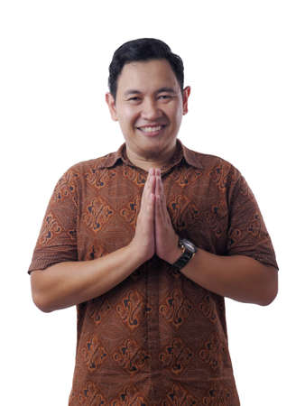 Portrait of young Asian man wearing batik shirt looking at camera, smiling and shows Asian greeting gesture isolated on white