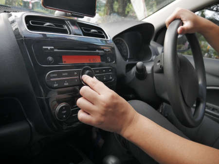 Close up image of driver's hand press button on car radio, listening music during trip concept