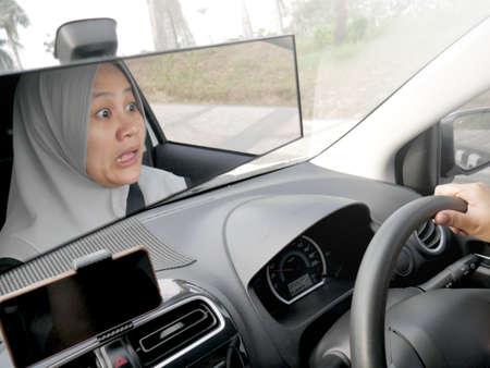 Portret van vrouwelijke Aziatische moslimbestuurder geschokt en in paniek die op het punt staat een ongeval te krijgen