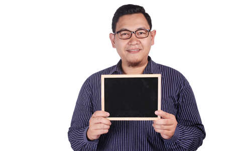 Portrait of young Asian man wearing eyeglasses and blue shirt smiling and presenting empty copy space blackboard