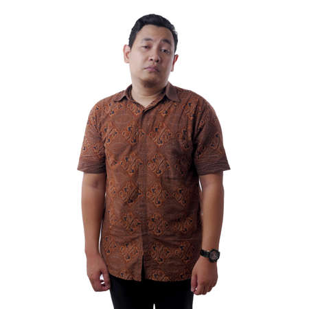 Portrait of young funny attractive Asian man wearing batik shirt shows lazy disgust unhappy bored mocking expression