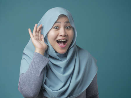 Portrait of Asian muslim woman smiling and doing hearing gesture, put hand on ear, listening carefully, against blue background