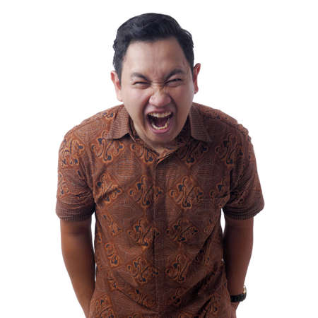 Portrait of  Asian man wearing batik shirt laughing hard and pointing forward, bully expression, isolated on white