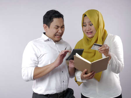 Portret azjatyckiej młodej pary muzułmańskiej sprawdzającej, analizując raport z zarządzania finansami rodzinnymi, młody mąż rodziny i żona zdezorientowani, że mają złe finanse