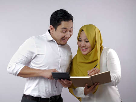 Portrait of Asian young muslim couple checking analyzing their family financial management report, young family housband and wife happy to see their financial plan Banque d'images