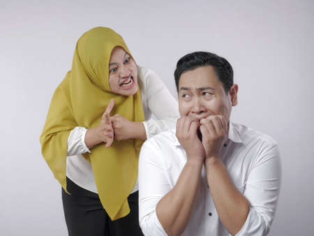 Portrait of funny Asian muslim couple having conflict, wife and husband fight, violence in family, husband afraid to his wife concept 스톡 콘텐츠