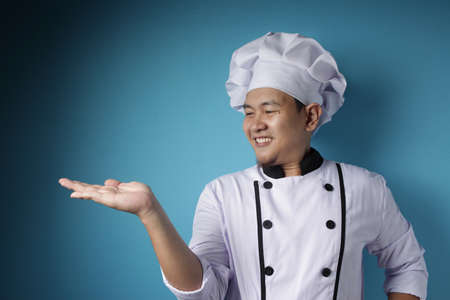 Portrait of happy smiling Asian chef pointing something on his empty hand, against blue background with copy space