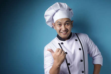 Portrait of happy smiling Asian chef pointing something on his side, against blue background with copy space