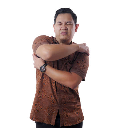 Young Asian man wearing batik shirt having shoulder pain. Close up body portrait, isolated on white