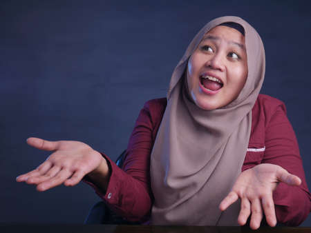 Portrait of Asian muslim woman shrugging shoulder, denial or I don't know gesture