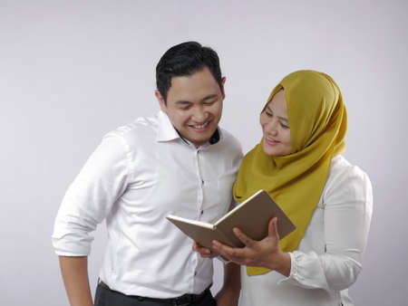 Portrait of Asian young muslim couple checking analyzing their family financial management report, young family housband and wife happy to see their financial plan
