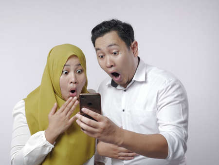 Portrait of Asian muslim couple shocked or surprised to see something on smart phone, big eyes and opened mouth expression