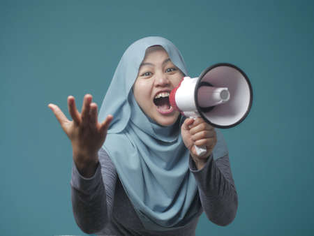 Young Asian muslim businesswoman wearing hijab screaming with megaphone, angry expression. Close up body portrait
