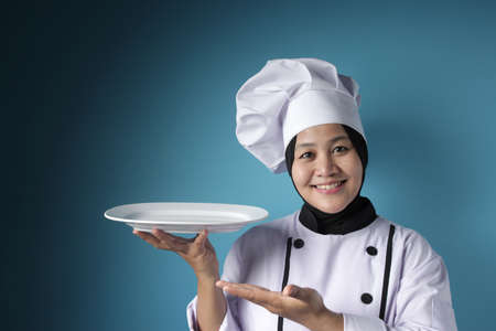 Portrait of Asian female chef looks happy and proud presenting something on her empty white plate, copy space meal menu concept Reklamní fotografie