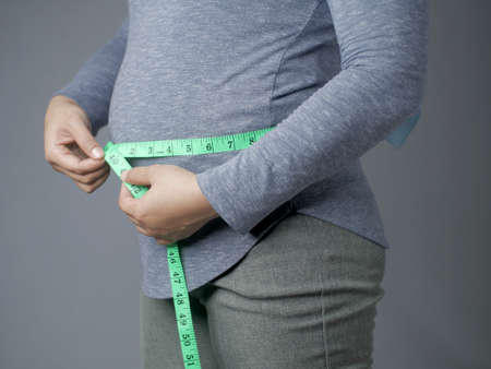Close up of woman mesuring her waistline with measurement tape, overweight woman, health concept