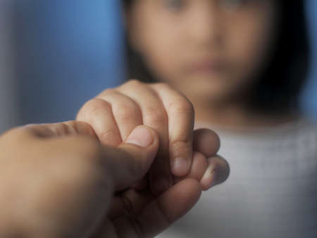 Little girl holds moms hand, love affection family concept, selective focus image Banque d'images