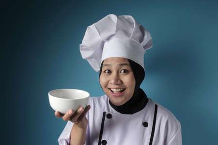Portrait of Asian female chef looks happy and proud presenting something on her empty white bowl, copy space meal menu concept Reklamní fotografie