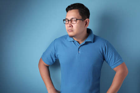 Portrait of arrogant young Asian man standing and shows upset cynically annoyed gesture, against blue background