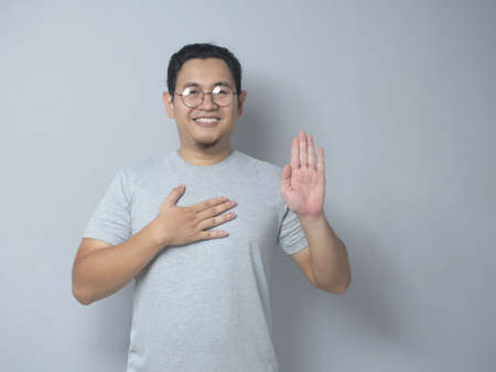 Portrait of happy Asian man making pledge gesture, hand on chest holding heart, making promise