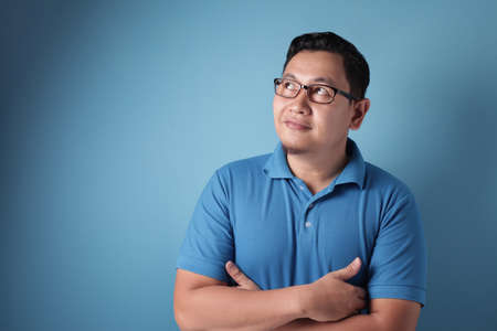 Portrait of young Asian man looked happy, thinking and looking up, having good idea. Half body portrait against blue wall with copy space