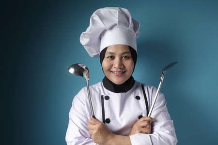 Portrait of Asian female chef shows ladle and spatula, ready to cook in the kitchen, kungfu chef in action