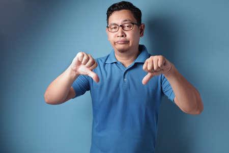 Porträt eines lustigen jungen asiatischen Mannes, der eine spöttische Geste mit synischem Gesicht macht und zwei Daumen nach unten über blauem Hintergrund zeigt