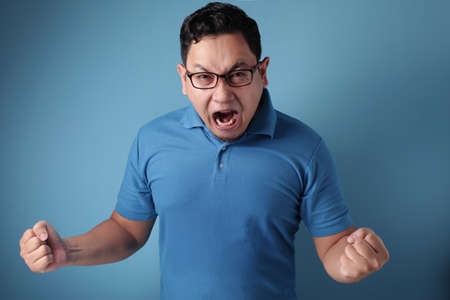 Young Asian man wearing blue shirt shouting because of anger. Against blue background