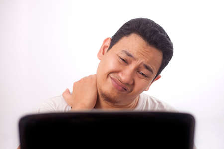 Portrait of young Asian man looked tired and suffer from stiffed neck pain after working on laptop for too long