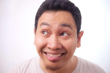Headshot portrait of funny young Asian man smiling and thinking something naughty, stupid mocking expression, close up headshot portrait