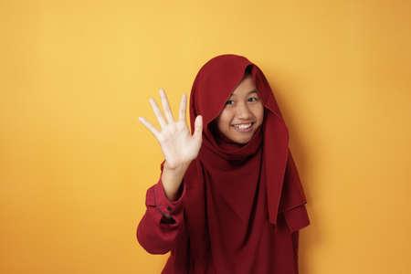 Ritratto di felice musulmana asiatica adolescente sorridente e salutando la telecamera, indossando hijab rosso su sfondo giallo