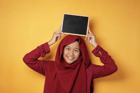 Portrait of smart young cute teenage Asian muslim girl wearing hijab smiling at camera while holding and showing empty blackboard or chalk board against yellow background, copy space