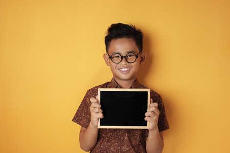Retrato de niño asiático lindo joven inteligente sonriendo a la cámara mientras sostiene y muestra la pizarra vacía o pizarra contra el fondo amarillo, espacio de copia Foto de archivo