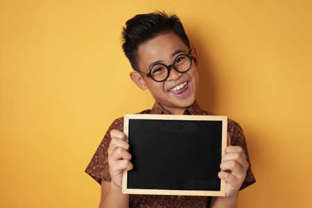 Portrait of smart young cute Asian boy smiling at camera while holding and showing empty blackboard or chalk board against yellow background, copy space