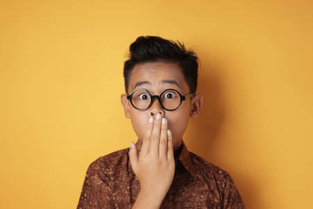 Portrait of funny young Asian boy looking at camera with big eyes covering his mouth, shocked surprised expression against yellow background
