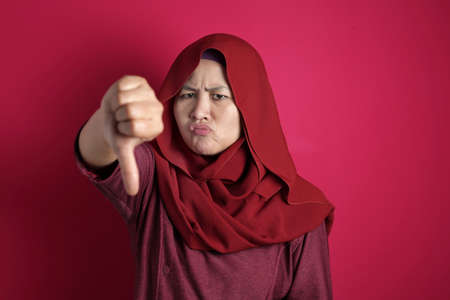 Portrait of muslim businesswoman boss manager leader lady looked angry while showing thumb down gesture, against red background