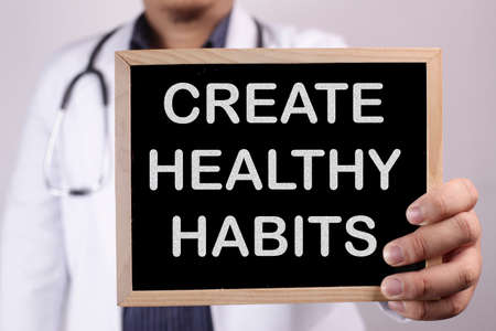 Create Healthy Habits. Male doctor holds chalkboard with health typography quotes written on it. Health and Medical Concept